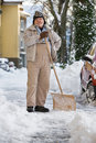 Senior Shovelling Snow Stock Photo