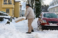 Senior Shovelling Snow Stock Images