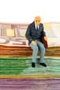 Senior sitting on bills symbolic photo for retirement and old age figure of an old man a stack of Royalty Free Stock Image