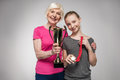 Senior sportswoman and girl holding trophy and medal on grey