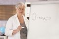 Senior teaching chemistry in school drawing molecular formulas on whiteboard Stock Photo