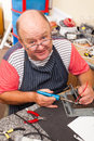 Senior technician workshop happy working with soldering iron in Royalty Free Stock Photography