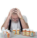 Senior with too many prescriptions sitting behind a lot of pill bottles holding his head in his hands isolated on white Stock Images