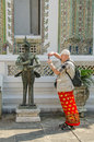 Senior tourist taking photo statue visiting royal palace complex Royalty Free Stock Image