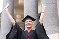 Senior university graduate cheerful female arms up Stock Image