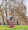 Senior in a wheelchair reading a book in park shot with tilt and shift lens Royalty Free Stock Photos