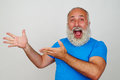 Senior white bearded man delighted and pointing at something wit is with both hands on his right side Royalty Free Stock Images
