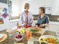 Senior woman and adult daughter cutting fresh vegetables on chopping board in kitchen smiling women Royalty Free Stock Photo