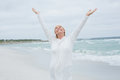 Senior woman with arms outstretched at beach casual standing the Royalty Free Stock Image