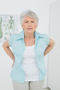 Senior woman with back pain in medical office portrait of a standing the Royalty Free Stock Photos