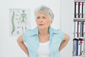 Senior woman with back pain in medical office standing the Stock Image