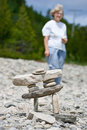 Senior woman behind Inukshuk statue on beach Stock Photo