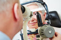 Senior woman behind slit lamp at women sitting optician Royalty Free Stock Photo