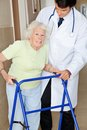 Senior woman being assisted by doctor portrait of a women using walker standing young Stock Photo