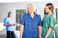 Senior woman being assisted by female caretaker in portrait of smiling women nursing home Stock Images