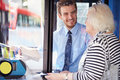 Senior woman boarding bus and buying ticket from driver Stock Photography
