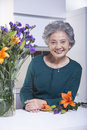 Senior woman beside bouquet of flowers in the kitchen portrait Stock Images