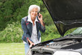 Senior woman with broken car standing behind a Royalty Free Stock Photo