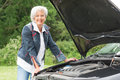 Senior woman with broken car standing behind a Stock Photo