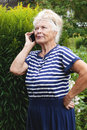 Senior woman calling on phone looking away in village garden flowers and solidago background Royalty Free Stock Photo