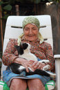 Senior woman and cat smiling sitting with a Stock Image