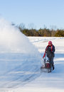 Senior woman clearing drive with snowblower lady using a on rural on windy day a cloud or blizzard of snow blowing in the air Stock Photos