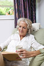 Senior woman with coffee cup reading book while relaxing on armchair at home women Royalty Free Stock Photos