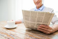 Senior woman with coffee reading newspaper at home age leisure and people concept close up of happy drinking and Stock Image