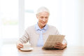 Senior woman with coffee reading newspaper at home age leisure and people concept happy drinking and Royalty Free Stock Image