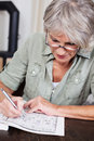 Senior woman completing a crossword puzzle sitting at table wearing reading glasses concentrating on Stock Photography