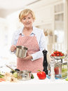 Senior woman cooking in the domestic kitchen Stock Images