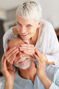 Senior woman covering husband eye to surprise him Royalty Free Stock Photography