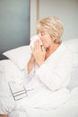 Senior woman covering nose while sneezing in bedroom Royalty Free Stock Photo