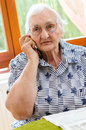 Senior woman dialling number on mobile phone sitting in chair Royalty Free Stock Images
