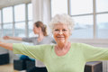 Senior woman doing aerobics exercise at gym two women stretching and workout women with her trainer in background during physical Royalty Free Stock Photo