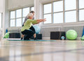 Senior woman doing exercise with her personal trainer women at gym gym instructor assisting elder women in workout Royalty Free Stock Image