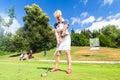 Senior woman doing tee stroke on golf course Royalty Free Stock Photo