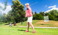 Senior woman doing tee stroke on golf course Royalty Free Stock Photo