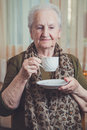 Senior woman drinking coffee alone in her house Stock Images