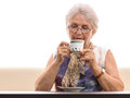 Senior woman drinking coffee isolated white old in glasses with a cup of or tea near her lips sitting on a sofa on background copy Stock Photography