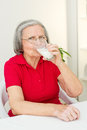 Senior woman drinking milk senir sitting at the table and Royalty Free Stock Photography