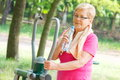 Senior woman drinking water after exercise on outdoor gym, healthy lifestyle
