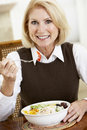 Senior Woman Eating Dinner, Smiling At The Camera Royalty Free Stock Photo