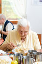 Senior woman eating her lunch at home Stock Images