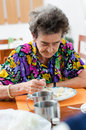 Senior woman eating her lunch at home Royalty Free Stock Photography