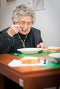 Senior woman eating her lunch at home Royalty Free Stock Image