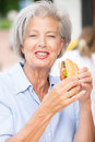 Senior woman eating smiling some fish Royalty Free Stock Image