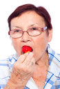 Senior woman eating strawberry Stock Photography