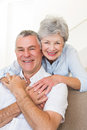 Senior woman embracing husband in house portrait of happy women Stock Photography