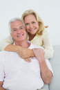 Senior woman embracing man from behind at home portrait of a happy women men Royalty Free Stock Images